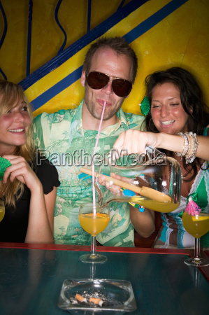 man and two women drinking in