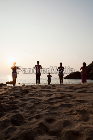 women practicing yoga on beach at