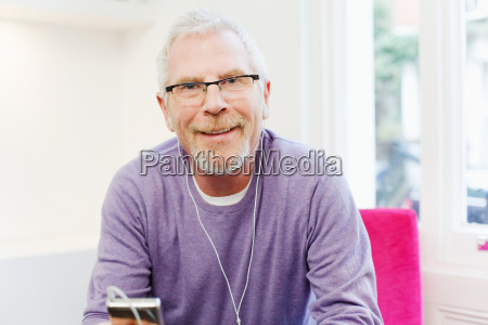 mature man listening to mp3 player