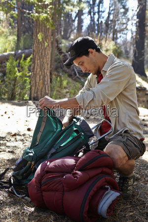 young man in forest unpacking camping