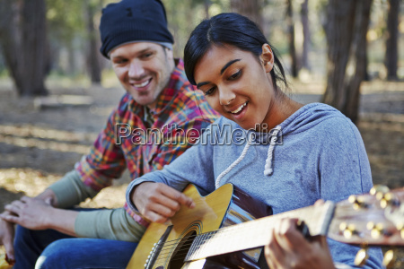 young couple in forest playing acoustic