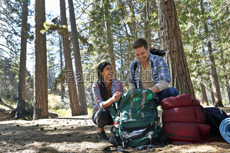 young couple unpacking camping rucksack in