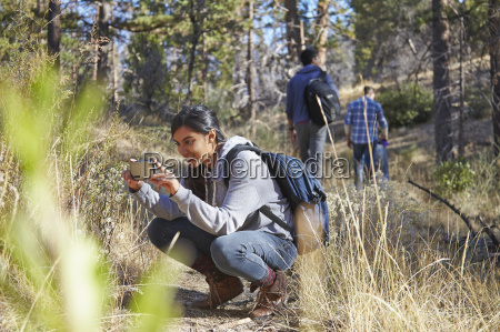 young female hiker photographing on smartphone