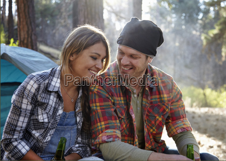 young couple chatting by campfire in