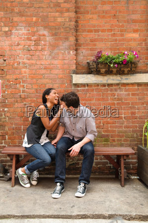 happy couple sitting on bench