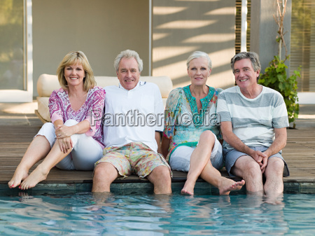 mature friends by swimming pool