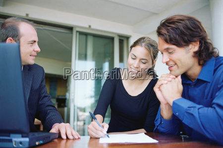 couple and financial adviser signing paperwork