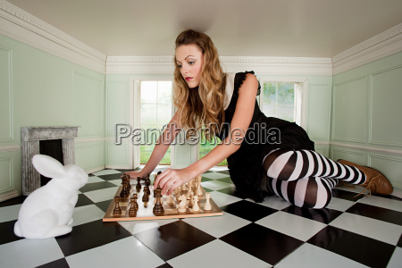 young woman playing chess with rabbit