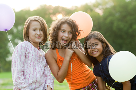 girls at birthday party holding balloons