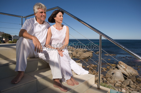 mature couple sitting by the sea