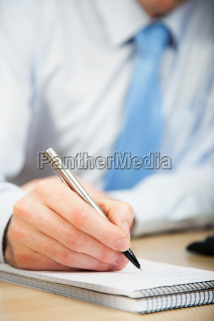 office worker making notes in notebook
