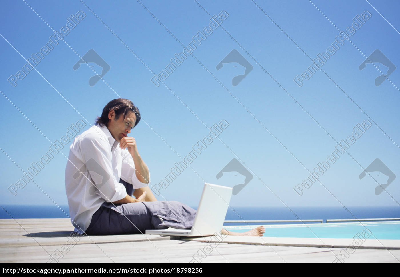 man, with, laptop, by, swimming, pool - 18798256