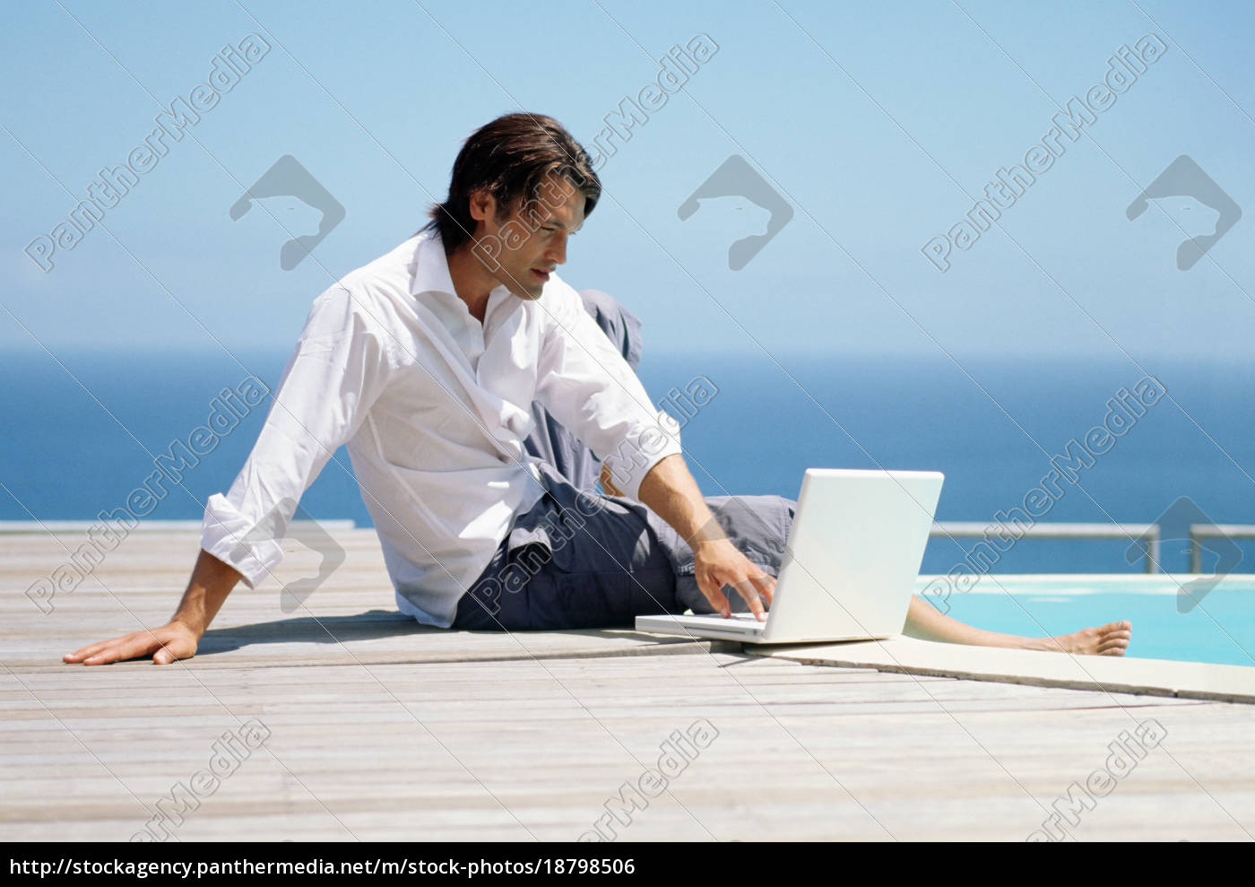 man, with, laptop, by, swimming, pool - 18798506