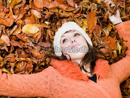 woman lying on autumn leaves