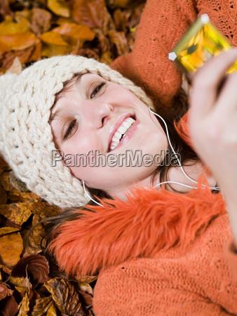 woman listening to music on autumn