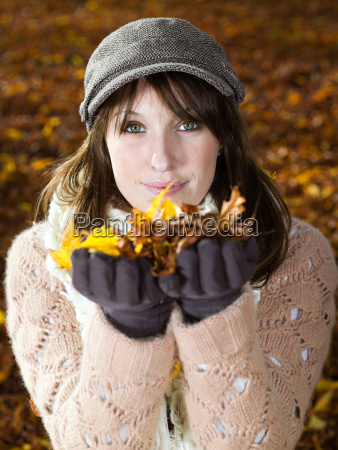 young woman holding autumn leaves