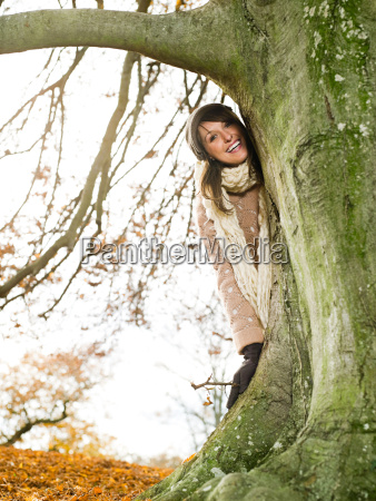 smiling woman standing behind a tree