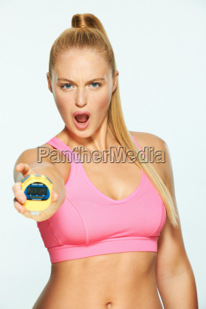 young woman holding stopwatch and shouting