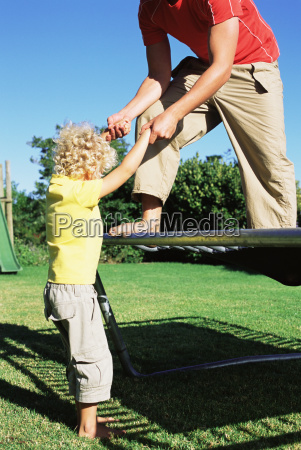 father helping son onto trampoline