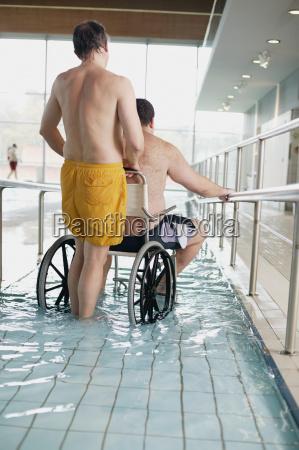 two men entering swimming pool