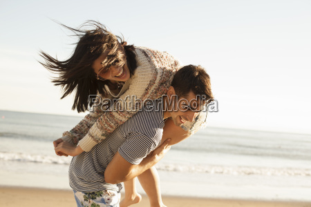 young couple fooling around on beach