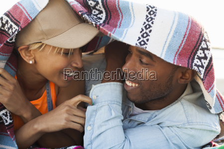young couple laughing together under picnic
