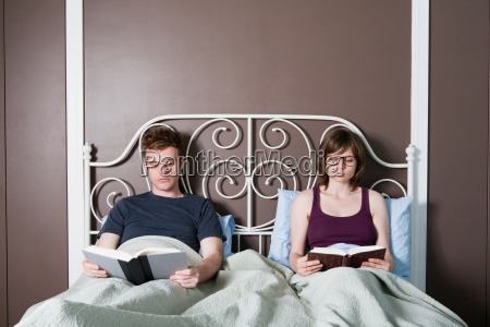 young couple reading in bed