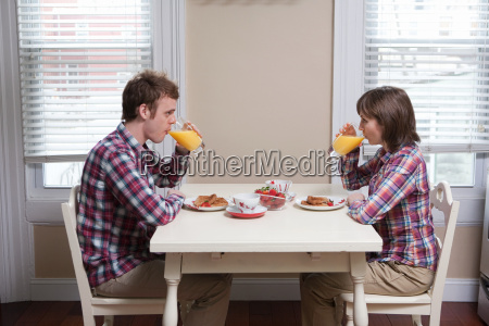 young couple drinking orange juice at