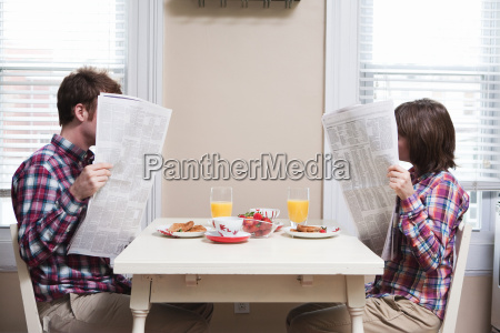 young couple reading newspapers at kitchen