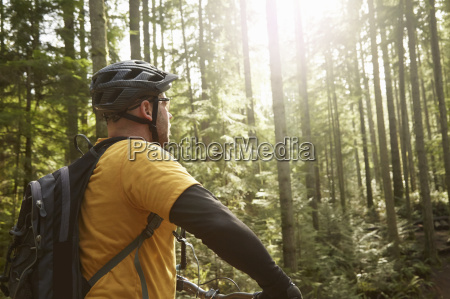 mature man riding bike in forest