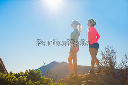 two female trail running friends looking