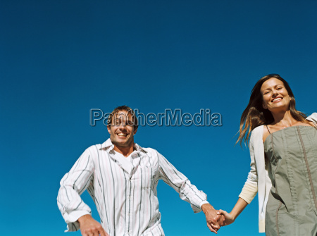 couple holding hands and running