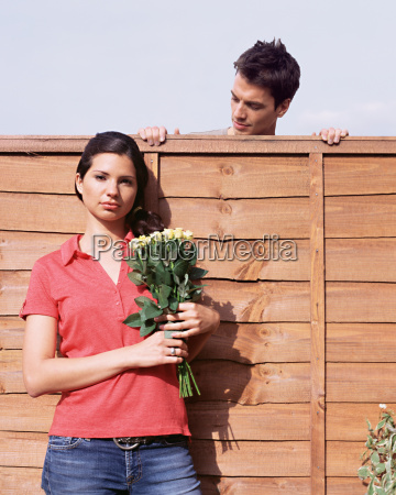 man looking at woman over garden