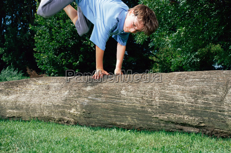 boy jumping over a log