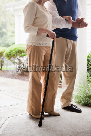 senior couple standing with walking stick