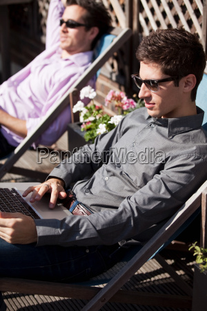 two, men, sunbathing, on, deck, chairs - 18809560