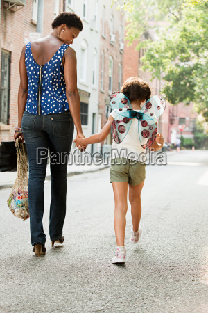 mother and daughter walking along street
