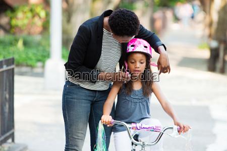mother adjusting daughters bicycle helmet