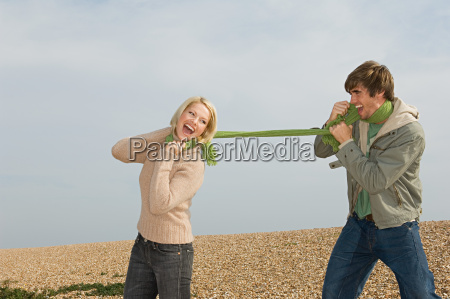 couple playing with scarf