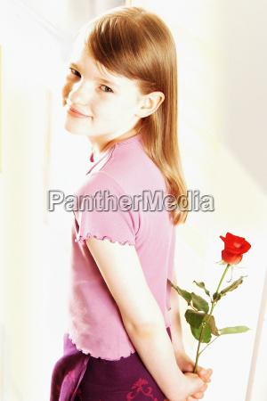 smiling girl holding red rose