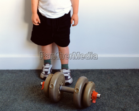 young boy with dumbbell