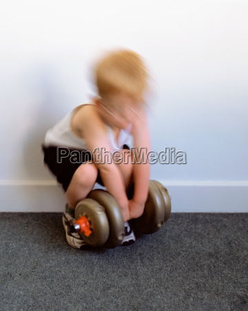 young boy lifting dumbbell