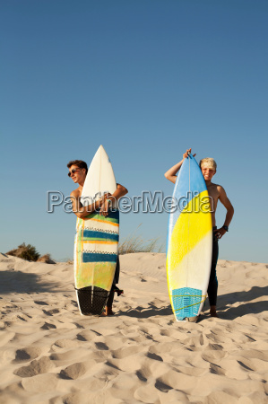 two young men standing behind surfboards