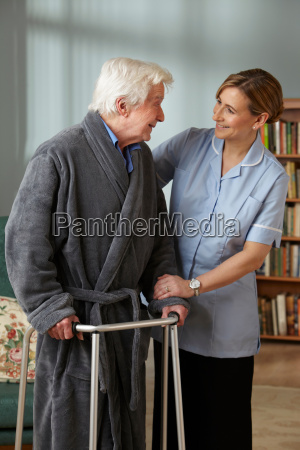 carer assisting senior man using walking