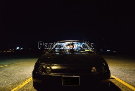 woman sitting in car at night