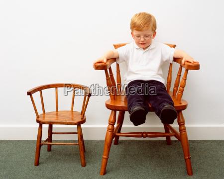 young boy sitting on big chair