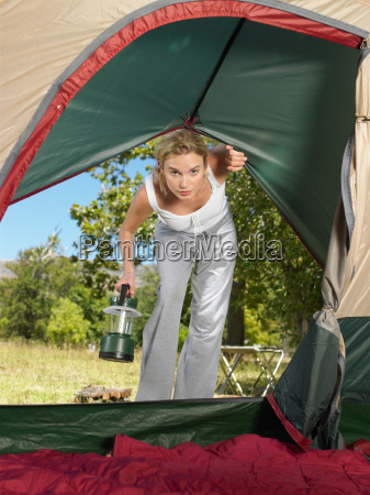 young woman looking into tent