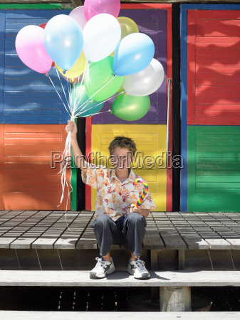 boy on step with balloons