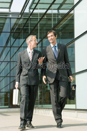 two businessman walking alongside office building