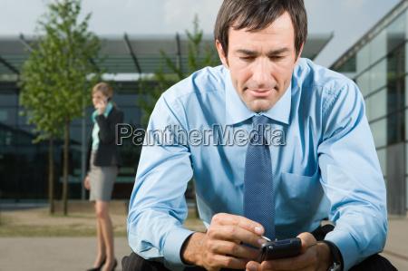 man using handheld computer outdoors